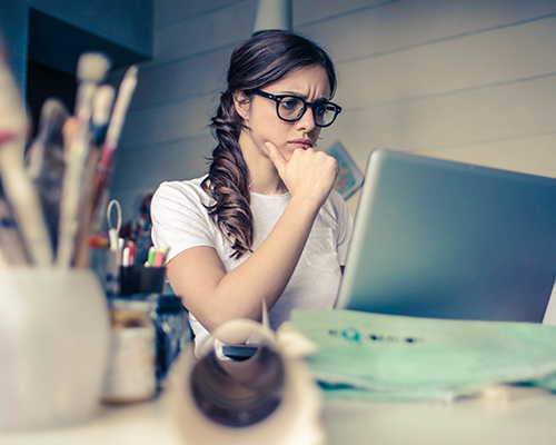 This is a photo of a woman sitting at a laptop looking concerned.