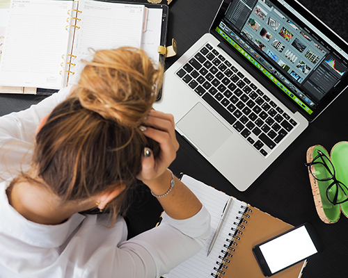 This is a photo of a women sitting at a laptop with her head in her hands.